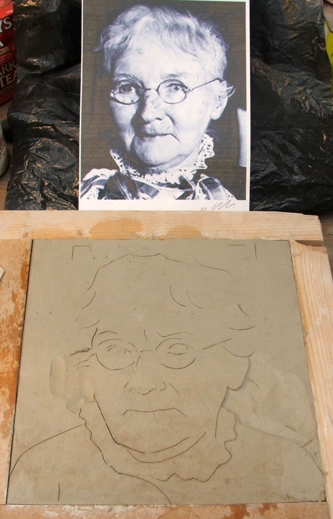 carving the relief image in clay