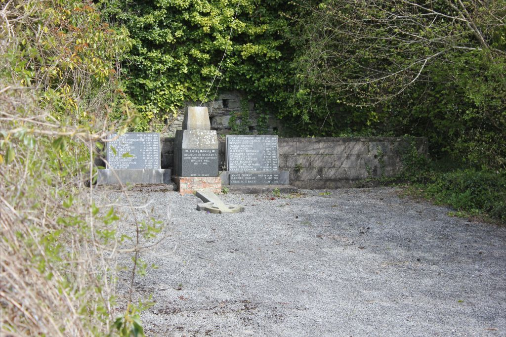 "Inaccessible Magdalene burial plot, Sunday's Well Cork.   Plaque beneath broken cross reads: ""A memorial to the Residents of St. Mary's Good Shepherd Convent, Sunday's Well. 1873-1993"""