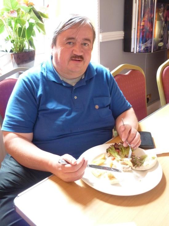 Committee member and website organiser John Jefferies enjoys a quick meal during a break in proceedings.